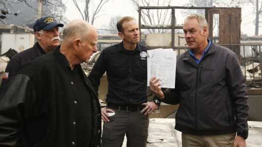 California Gov. Jerry Brown, second from left, looks at a students work book displayed by Interior Secretary Ryan Zinke, that was found during a tour of the fire ravaged Paradise Elementary School Wednesday, Nov. 14, 2018, in Paradise, Calif.