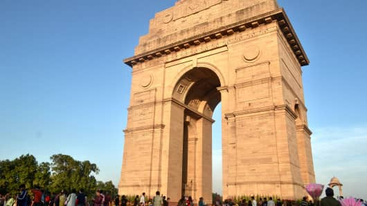 Visitors walk near the India Gate in New Delhi, India. India Gate was built in the memory of more than 90,000 Indian soldiers who lost their lives during the Afghan Wars and World War I.