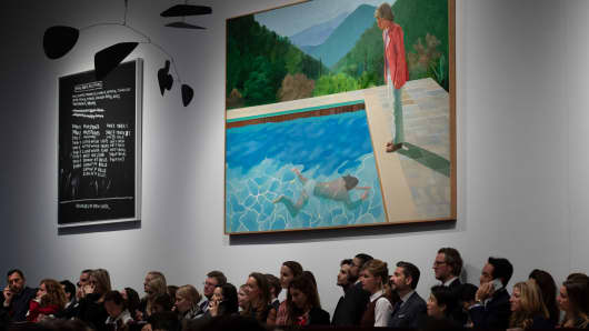 A crowd of people attend the sale where David Hockney's Portrait of an Artist (Pool with Two Figures) is displayed at Christie's in New York.