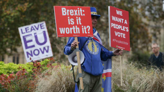 An Anti-Brexit campaigner Steve Bray (R) stands with placards  and a pro-Brexit supporter (L) stands with a placard demanding an immediate departure from the European Union.