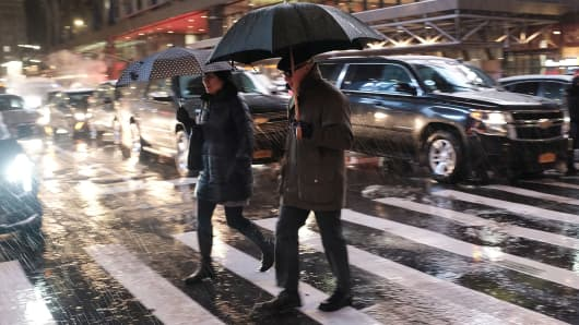 Pedestrians walk through a wintery mix of snow, rain and ice during the evening commute in Manhattan on November 15, 2018 in New York City.