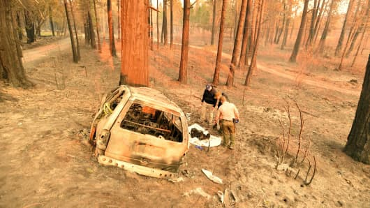 Yuba and Butte County Sheriff officers inspect remains near a burned out vehicle off a dirt road in Concow, California on November 11, 2018 after the Camp fire ripped through the area.