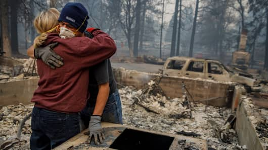 Couple hugs after they manage to recover keepsake bracelet in the rubble of their destroyed home, after the Camp Fire razed through Paradise, California, on Nov. 15, 2018.