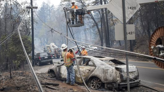 AT&T Inc. workers repair phone lines as a burned-out vehicle sits on a road during the Camp Fire in Paradise, California, U.S., on Tuesday, Nov. 13, 2018.