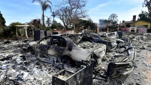 The remains of burnt down homes and vechicles resulting from the Woolsey Fire are seen on Busch Drive in Malibu, California on November 13, 2018.