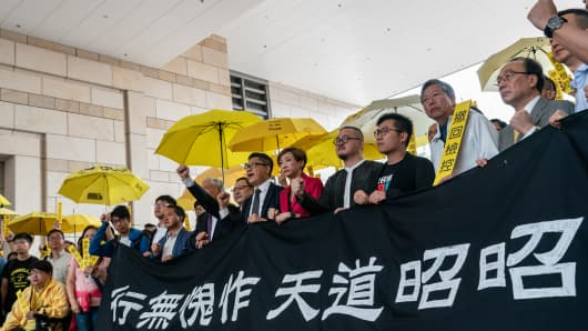 Pro-democracy activists Chung Yiu-wa, Cheung Sau-yin, Lee Wing-tat, Chu Yiu-ming, Benny Tai, Chan Kin-man, Tanya Chan, Shiu Ka-chun and Raphael Wong pose poses for a photograph during a rally outside West Kowloon Court on November 19, 2018 in Hong Kong.
