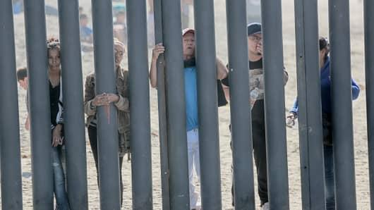 Honduran caravan members look through through the fence at the US-Mexico border wall at Friendship park in San Ysidro, California on November 18, 2018.