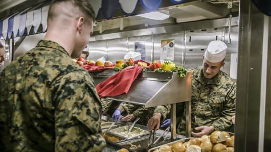 U.S. Marines and sailors are served a Thanksgiving meal aboard the USS Oak Hil.