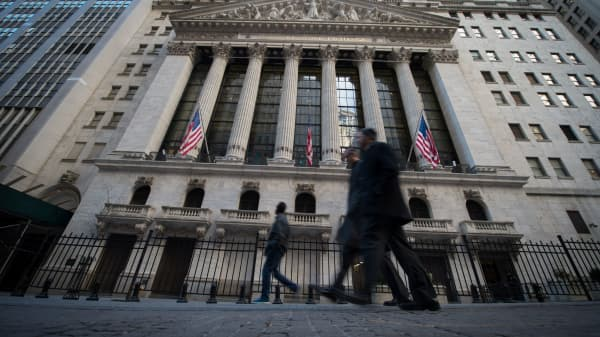 Pedestrians walk past the New York Stock Exchange before the closing bell in New York.