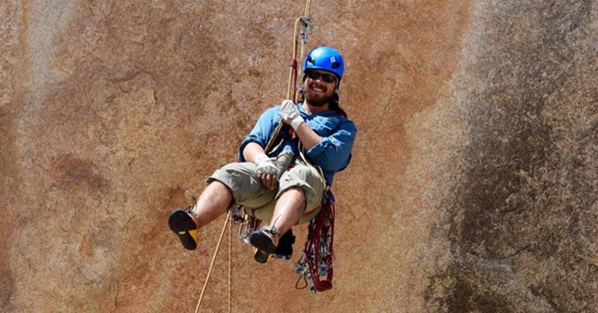 John Sweat rappelling off a climb
