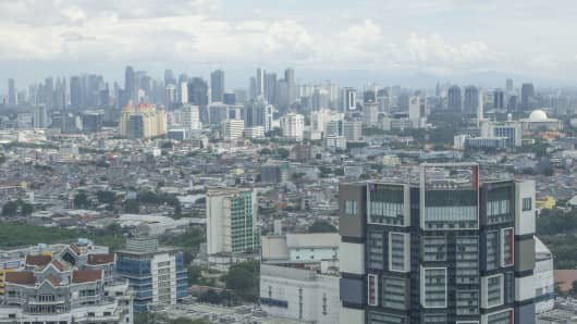 A bird's eye view of commercial and residential buildings stand as seen from a skyscraper during construction development in Central Jakarta.