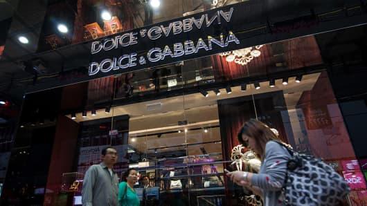 Shoppers walk past a Dolce & Gabbana store in Hong Kong