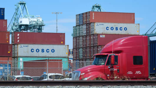 A container delivery truck passes containers stacked at the Port of Long Beach in Long Beach, California on July 6, 2018, including some from COSCO, the Chinese state-owned shipping and logistics company. -