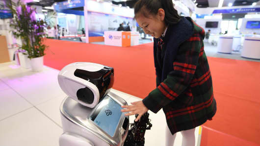 A girl plays a finger-guessing game with a robot during the United Nations World Geospatial Information Congress (UNWGIC) at the Deqing International Exhibition Centre on November 20, 2018 in Deqing County, Zhejiang Province of China.