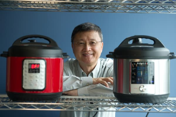Instant Brands CEO Robert Wang poses with two Instant Pot products.