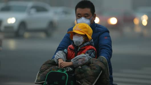 A man and a child wearing breathing masks are seen on an electric vehicle in smog on November 14, 2018 in Beijing, China.