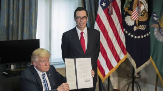 U.S. President Donald Trump, with Secretary of Treasury Steven Mnuchin, displays a signed financial services Executive Order during a ceremony in the US Treasury Department building.