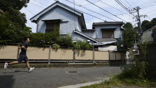 A man runs past a vacant house in the Yato area of Yokosuka City, Kanagawa Prefecture, Japan