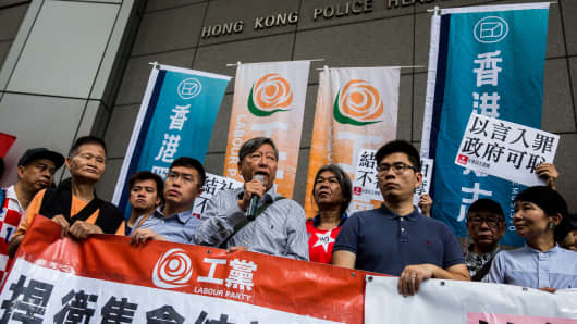 Pro-democracy lawmaker Au Nok-hin, former lawmakers and pro-democracy activists Lee Cheuk-yan and Leung Kwok-hung, also known as 'Long Hair', attend a protest against the Hong Kong police seeking a ban on the pro-independence Hong Kong National Party, outside the police headquarters in Hong Kong on July 18, 2018.