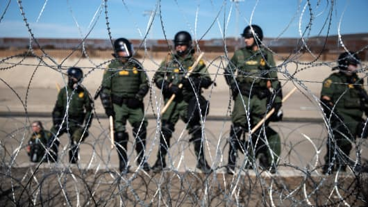 U.S. Customs and Border Protection (CBP) officers stand guard on the U.S. side of the border as barbed wire lines along the US and Mexico border in Tijuana, Mexico, on Sunday, Nov. 25, 2018.