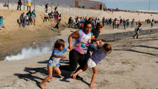 A migrant family from Honduras, part of a caravan of thousands traveling from Central America en route to the United States, runs from tear gas released by U.S. border patrol near the fence between Mexico and the United States in Tijuana, Mexico, November 25, 2018.