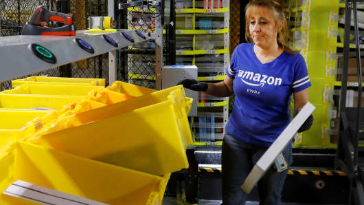 An Amazon employee works in the picking station for merchandise at the Amazon fulfillment center in Robbinsville, New Jersey, November 26, 2018.