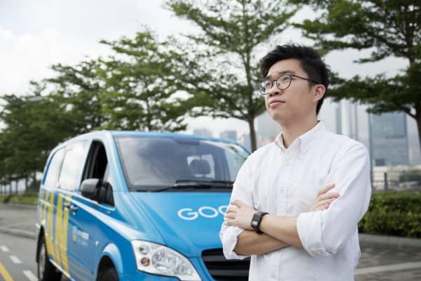 GoGoVan's founder and CEO Steven Lam up looks toward the Hong Kong city skyline