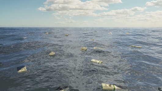 Large group of one hundred dollar bill stacks floating on surface of sea