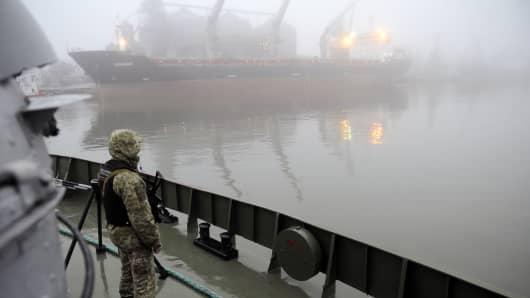 Ukrainian soldier stands guard aboard military boat called 'Dondass' moored in Mariupol, Sea of Azov port on November 27, 2018. - Three Ukrainian navy vessels were seized off the coast of Crimea by Russian forces, which fired on and boarded Kiev's ships after several tense hours of confrontation. Here's what is known about Sunday's incident.