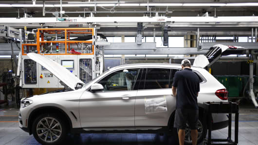 A worker applies final touches on a Bayerische Motoren Werke AG (BMW) sports utility vehicle (SUV) on an assembly line at the BMW Manufacturing Co. plant in Greer, South Carolina, U.S. on Thursday, May 10, 2018.