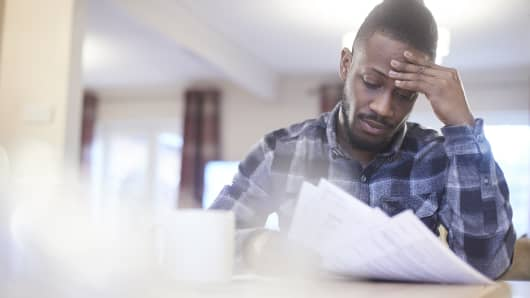 Worried young male reading through bank statements