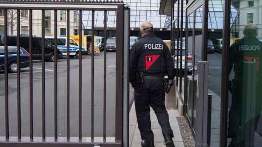 A police officer passes a gate outside the headquarters of Deutsche Bank AG in Frankfurt, Germany, on Thursday, Nov. 29, 2018.