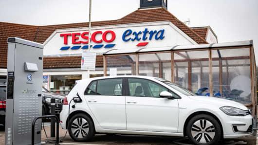 A Volkswagen car charging outside a Tesco supermarket.