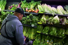 A produce worker stocks shelves near romaine lettuce (top shelf, right) at a supermarket in Washington, DC on November 20, 2018.