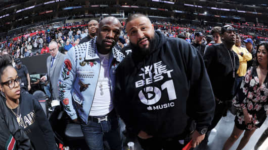 Floyd Mayweather Jr. talks with DJ Khaled after the game between the Golden State Warriors and the Los Angeles Clippers on February 20, 2016 at STAPLES Center in Los Angeles, California.