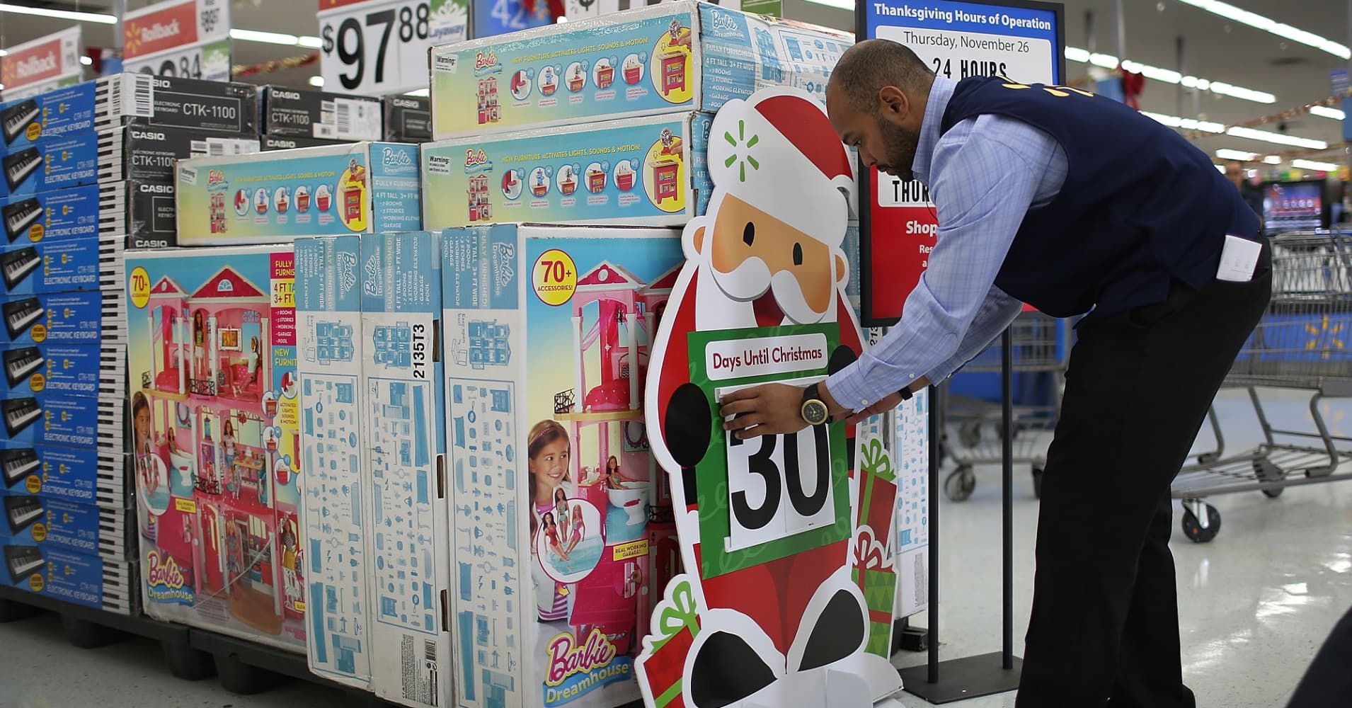 Jonathan Mary fixes the sign indicating that there are 30 more days until Christmas at a Walmart store in Miami, Florida.