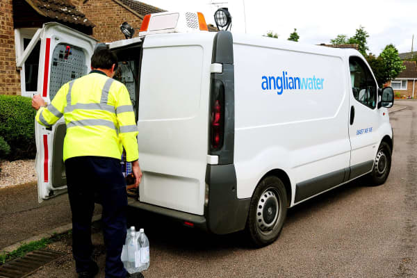 An Anglian Water official delivers water to residents in Northampton following a contamination scare.