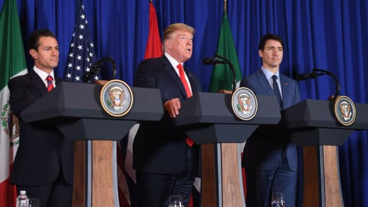 (L to R) Mexican President Enrique Pena Nieto, US President Donald Trump and Canadian Prime Minister Justin Trudeau deliver a statement on the signing of a new free trade agreement in Buenos Aires, on November 30, 2018.