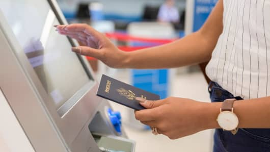 Unrecognizable traveler checks in at the airport by using a self serve kiosk.