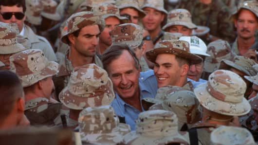 President George H.W. Bush shakes hands with US Army troops in Saudi Arabia during the Gulf War on Thanksgiving Day 1990.