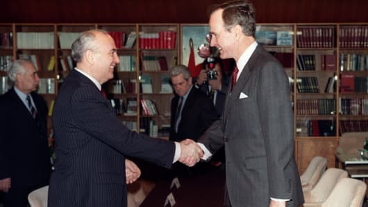 Soviet leader Mikhail Gorbachev (L) and US President George Bush (R) shake hands on December 02, 1989 on board the soviet cruise 'Maxim Gorki', shipdocked at Marsaxlokk harbour, before the start of their first summit meeting, just a few weeks after the fall of the Berlin Wall. This summit is viewed as the official end of the Cold War.