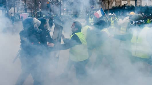 Demonstrators clash with riot police on the Champs Elysees avenue in Paris during a protest of Yellow vests (Gilets jaunes) against rising oil prices and living costs, on December 1, 2018.