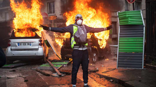 Protesters clashes with riot police on Foch avenue next to the Place de l'Etoile, setting cars ablaze during a Yellow Vest protest on December 1, 2018 in Paris, France. The 'Yellow Vest' is a protest movement without political affiliation that rallies against taxes and rising fuel prices.