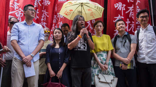 Hong Kong pro-democracy lawmaker Leung Kwok-hung (C), also known as 'Long Hair', is flanked by other pro-democracy lawmakers Lau Siu-lai (centre L), Tanya Chan of Civic Party (centre R) and Eddie Chu (R) as he speaks outside the Wan Chai district court in Hong Kong on July 31, 2017.