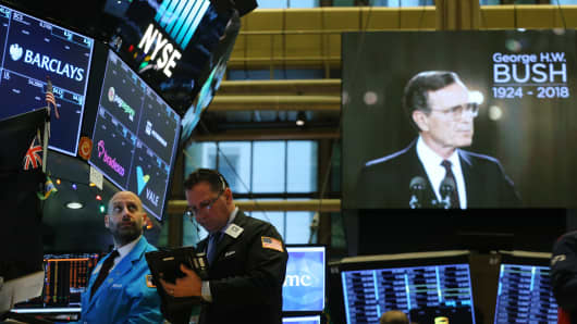 Traders work on the floor of the New York Stock Exchange (NYSE) as a picture of former President George H.W. Bush appears on a screen following a moment of silence on December 3, 2018 in New York City.