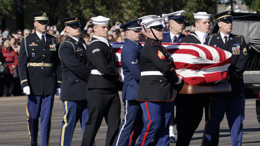 Joint services military honor guard carry the flag-draped casket of the remains of President George H.W. Bush during a departure ceremony to Washington D. C at Ellington Field on December 3, 2018 in Houston, Texas.