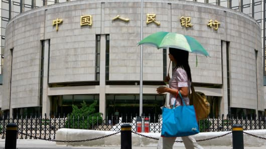 A pedestrian walks past the People's Bank of China, also known as China's Central Bank in Beijing, 22 August 2007.