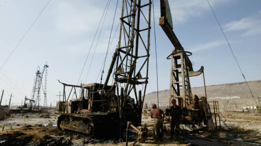 Azeri oil workers operate a large field of drilling rigs, outside the capital city of Baku.