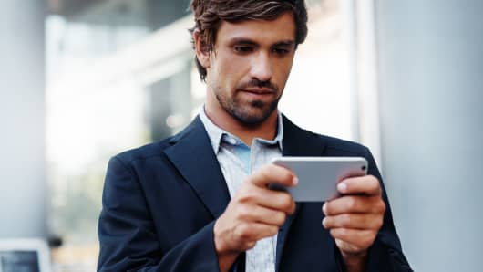 Shot of a young businessman using a smartphone while out in the city