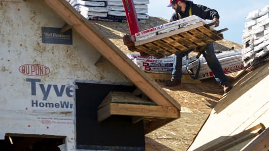 A contractor stacks roofing materials while working on a home under construction at the Toll Brothers Bowes Creek Country Club community in Elgin, Illinois.